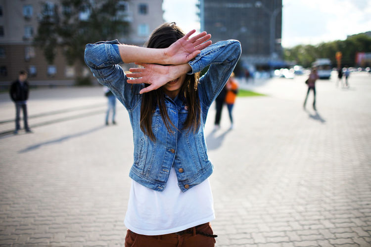 The girl stands on the city square and covers her face with her hands. The portrait is made in natural light. Casual Hands Jeans Life Life In Motion People Watching Square Casual Clothing Day Girl Hand Leasure Activity Lifestyles Look One Person One Woman Only Outdoor Outdoor Photography Outdoors People people and places People Photography Portrait Real People Summer