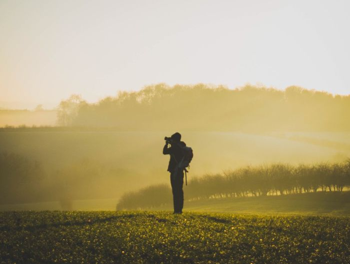 Photography Themes Standing Photographing Camera - Photographic Equipment Landscape Nature Field Full Length Nature_collection One Person Real People Men Holding Outdoors Sky Grass Beauty In Nature Digital Camera Tree Photographer Countryside Leisure Activity Foggy Hazy  EyeEm Best Shots The Great Outdoors