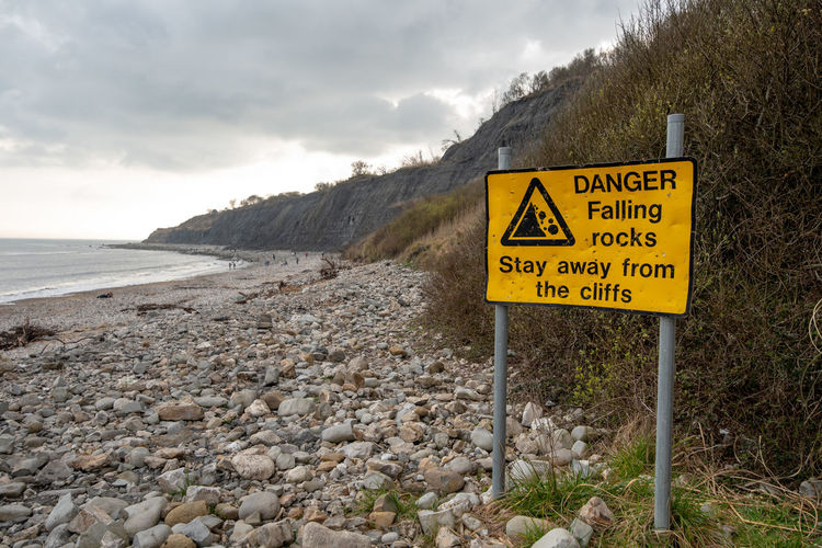 A bright yellow Danger sign warning of Falling Rocks from the cliffs along the Lyme Regis fossil beach, Dorset, UK. Cloud - Sky Communication Day Guidance Land Mountain Nature No People Outdoors Road Rocks Scenics - Nature Script Sign Sky Text Tranquility Warning Warning Sign Water Western Script Yellow