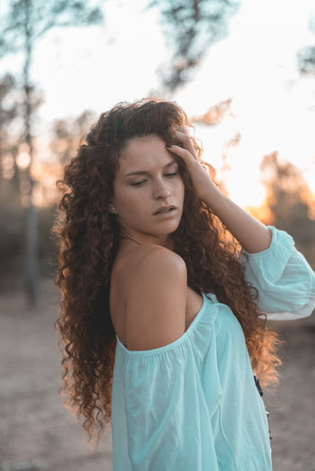 Hairstyle One Person Hair Long Hair Young Adult Curly Hair Young Women Brown Hair Focus On Foreground Lifestyles Beautiful Woman Casual Clothing Leisure Activity Beauty Women Looking Real People Front View Standing Contemplation Frizzy Teenager