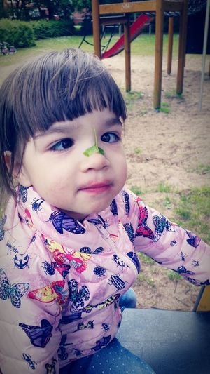 Cute girl looking at leaf on her nose while sitting at playground