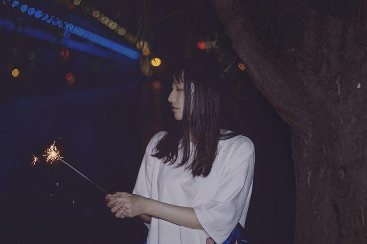 Woman holding lit sparkler at night