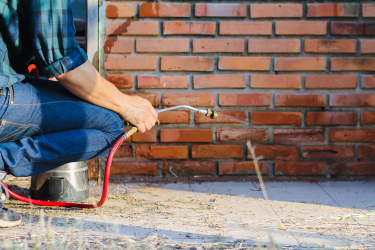 Low section of man working on brick wall