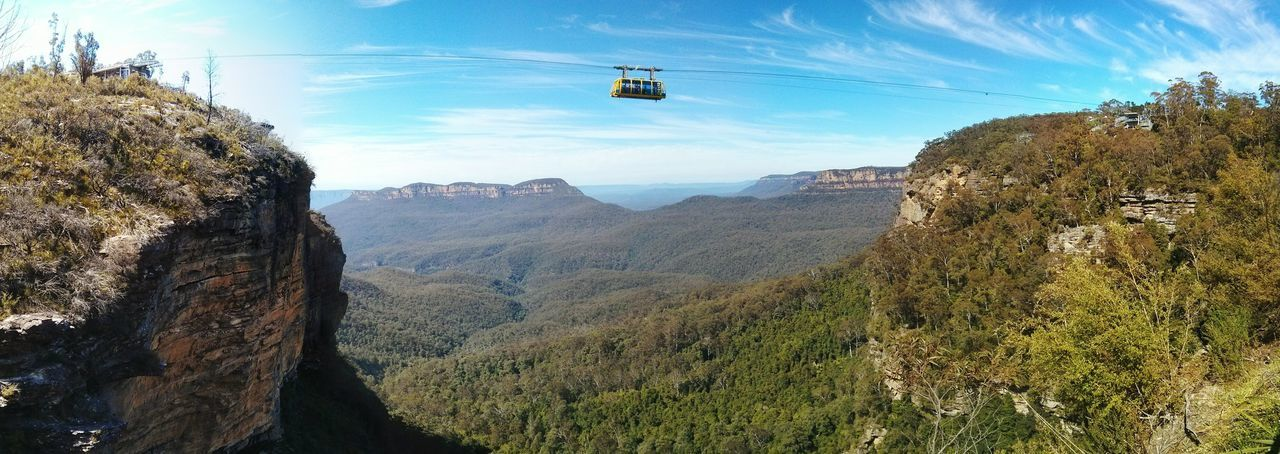 Panoramic Shot Of Overhead Cable Car Over Landscape Against Sky