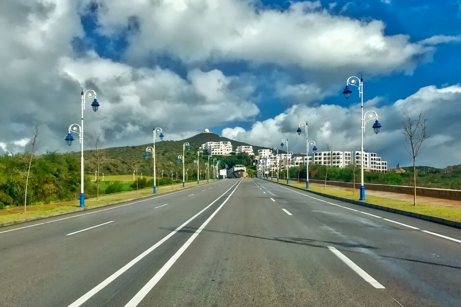 Boulevard at Martil in Morocco. Boulevard Buildings Bushes Clouds Day Grass Martil Morocco Mountain No People Outdoors Radio Station Sky Street Lamps The Way Forward Transportation Trees