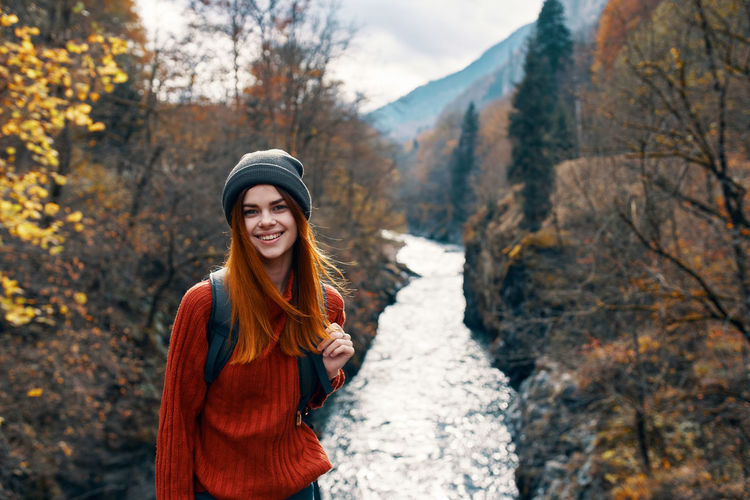 Portrait of smiling young woman standing by trees during autumn