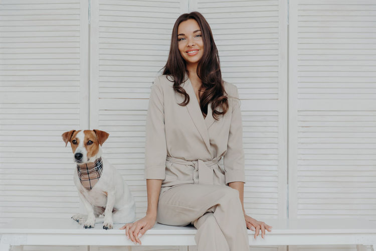 Portrait of smiling woman with dog sitting on bench