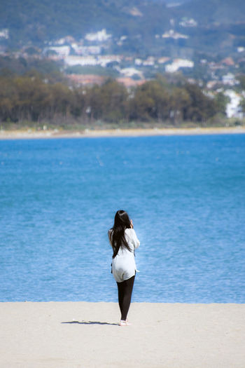 Rear view of woman standing on sand against sea at beach