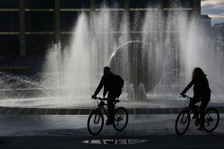 Man riding bicycle on fountain in city