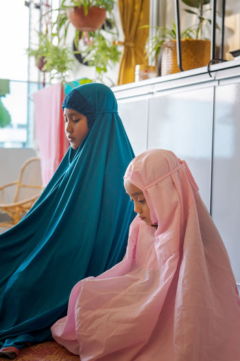 Cute girls in hijab praying at home