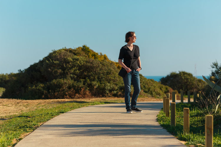 Woman Standing On Footpath Against Clear Sky