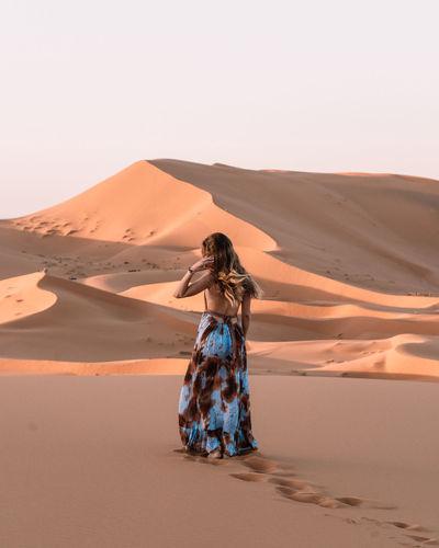 Woman standing on sand dune in desert