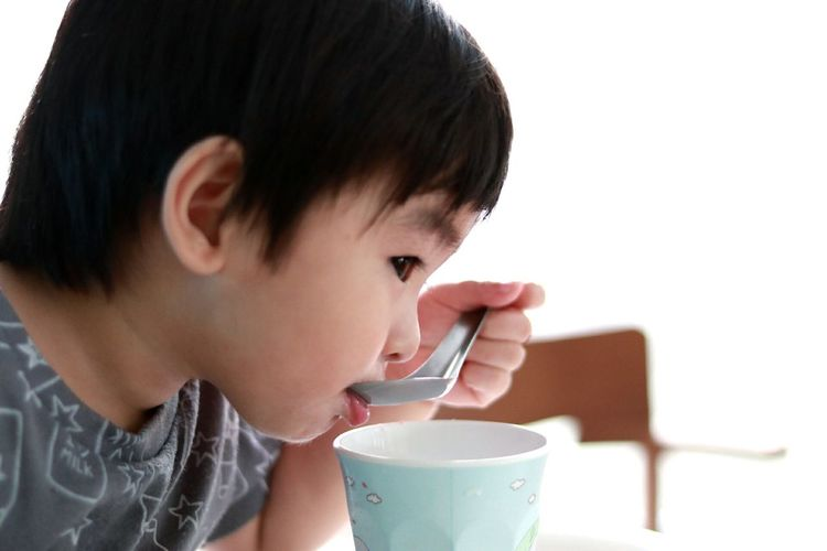 Side view of boy drinking milk from spoon at home