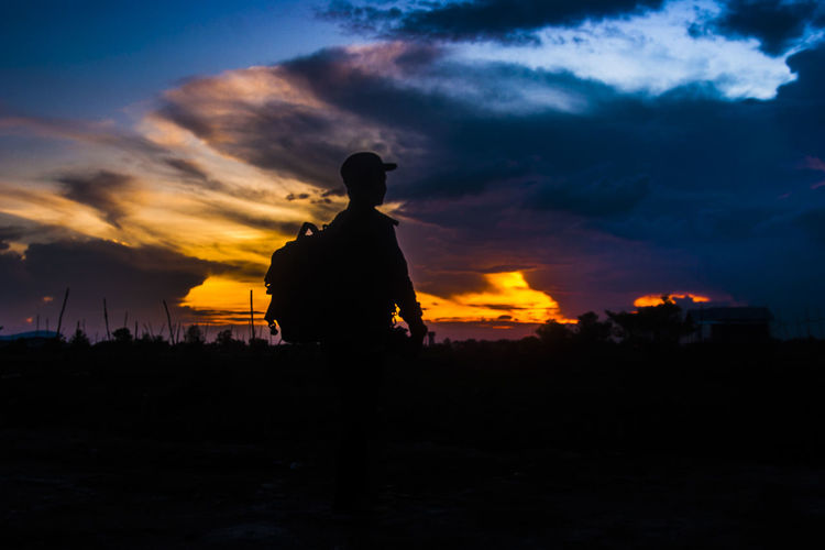 looked at the evening sky - Palangka Raya, Central Kalimantan, Indonesia Silhouette Sunset Sky Cloud - Sky Orange Color Men Nature Standing Land One Person Real People Rear View Lifestyles Outdoors Leisure Activity Beauty In Nature Scenics - Nature Field Dramatic Sky