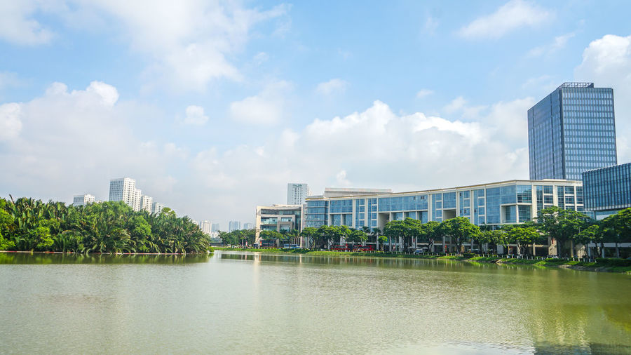 Panoramic view of buildings by lake against sky