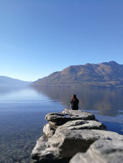 Rear View Of Woman Sitting On Rock At Lakeshore Against Clear Blue Sky