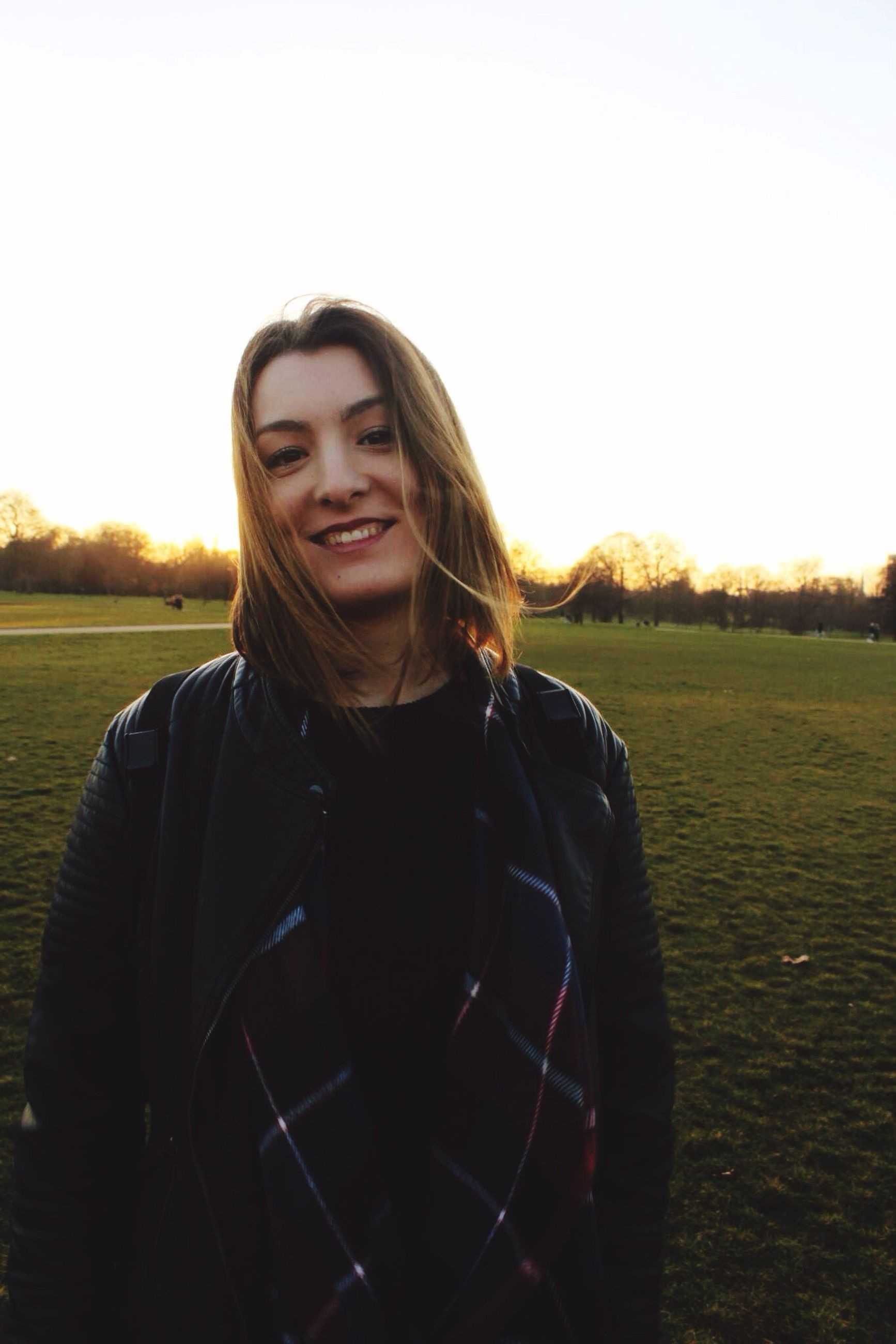 lifestyles, young adult, leisure activity, casual clothing, person, portrait, looking at camera, clear sky, front view, standing, waist up, young women, smiling, sunset, three quarter length, copy space, field, long hair