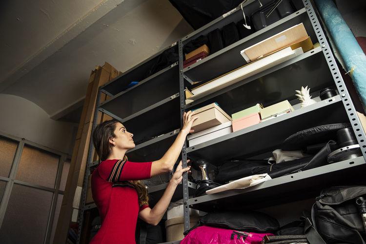 Low angle view of woman placing box on shelf