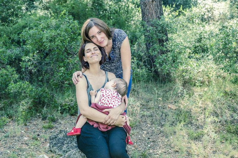 Full length portrait of happy mother and daughter in park