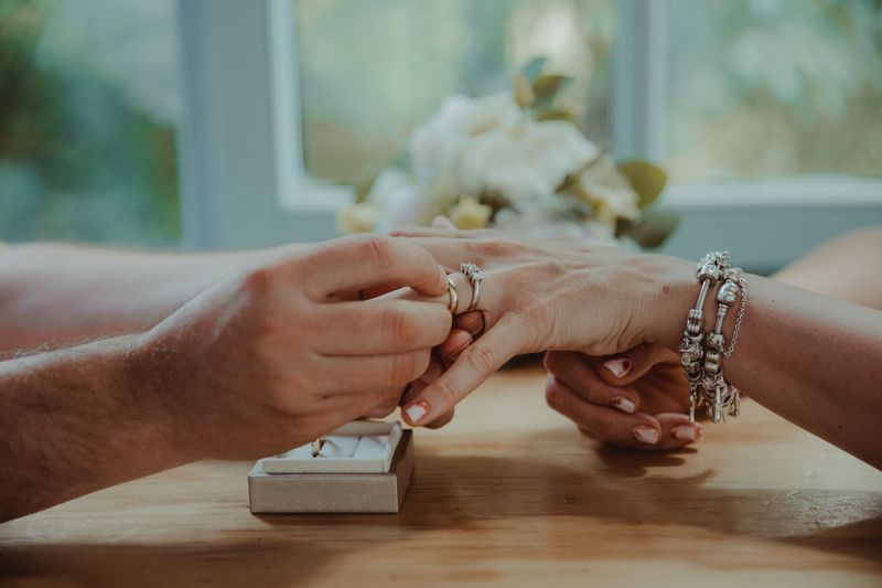 Midsection of couple holding hands on table