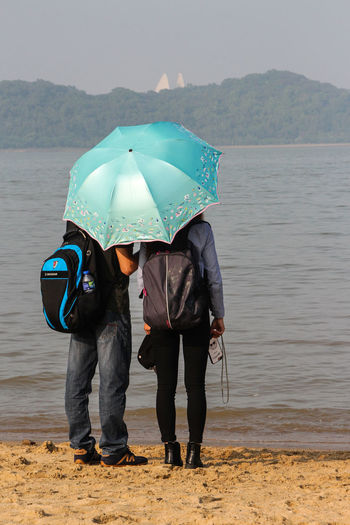 Rear View Of Couple With Umbrella Standing At Beach Against Sky