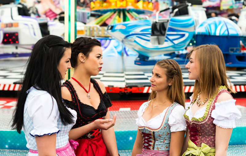 Friends Discussing At Amusement Park During Oktoberfest