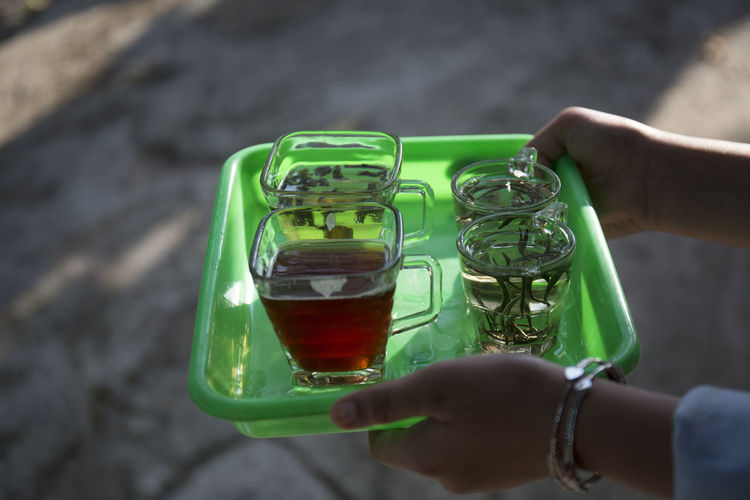 Tea Drink Human Hand Hand Holding Human Body Part One Person Real People Drink Focus On Foreground Close-up Food And Drink Green Color Day Refreshment Body Part Leisure Activity Lifestyles Unrecognizable Person Outdoors Glass Finger Served Tea Cup