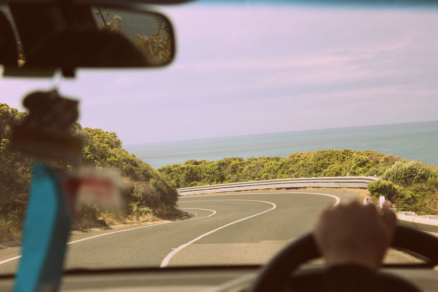 Curve in the road. Car Transportation Mode Of Transport Travel Land Vehicle Rear-view Mirror Sky Day One Person Vehicle Interior Driving The Way Forward Vehicle Mirror Road Outdoors People Human Hand Great Ocean Road Travelling Victoria Ocean View Ocean Curved Road Summer Road Trip