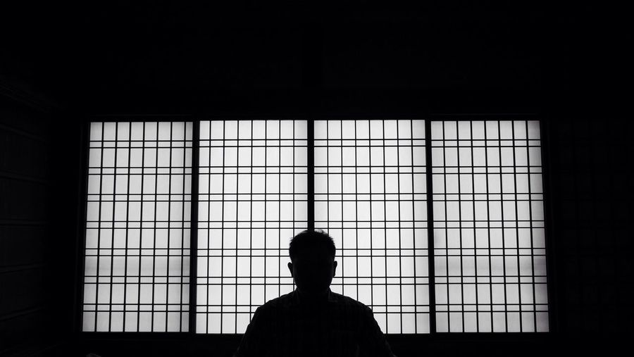 Silhouette Of Man Against Window