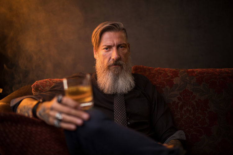 Portrait of an attractive business man with a glass of whiskey Relaxing Smoke Tattooed Adult Alcohol Beard Bearded Contemplation Drink Drinking Food And Drink Glass Hipster Holding Jewelry Mature Adult Mustache One Person Portrait Refreshment Scotch Sitting Studio Shot Tattoo Whiskey