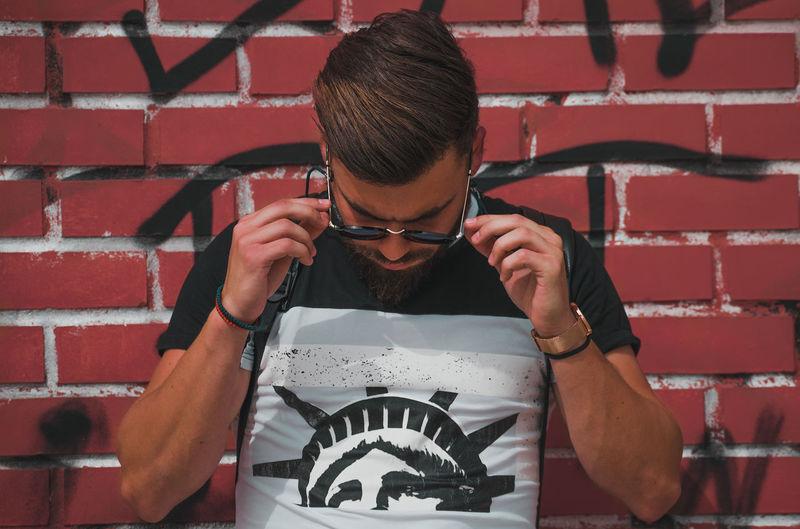 Full length of man holding eyeglasses against wall