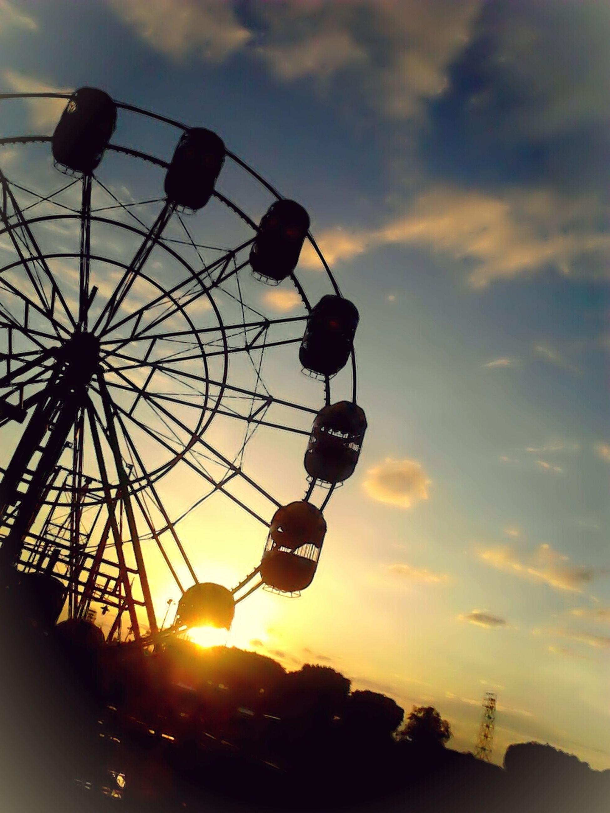 low angle view, sky, sunset, silhouette, sun, cloud - sky, ferris wheel, amusement park, amusement park ride, orange color, cloud, lighting equipment, street light, nature, outdoors, arts culture and entertainment, lens flare, cloudy, beauty in nature, no people