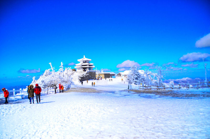 Tourists on snow covered landscape