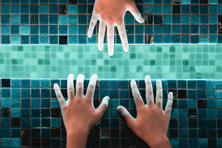 Directly above shot of hands in illuminated swimming pool