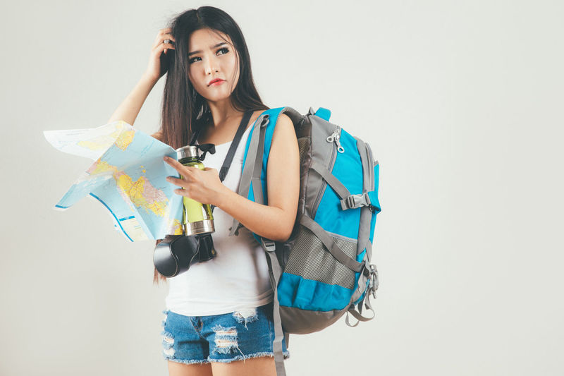 Travel Bagpacker Bagpacking Trip Beautiful Woman Casual Clothing Copy Space Front View Hairstyle Holding Indoors  Leisure Activity Lifestyles Looking At Camera One Person Portrait Standing Studio Shot Three Quarter Length White Background Women Young Adult Young Women