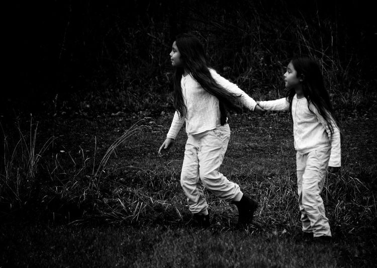 Full Length Of Siblings Holding Hands On Grassy Field