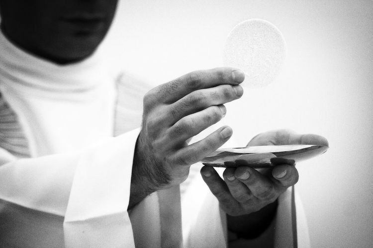 Midsection Of Priest Giving Communion In Church