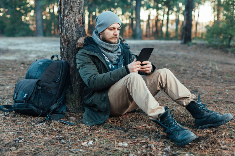 Full length of male hiker using digital tablet while sitting in forest