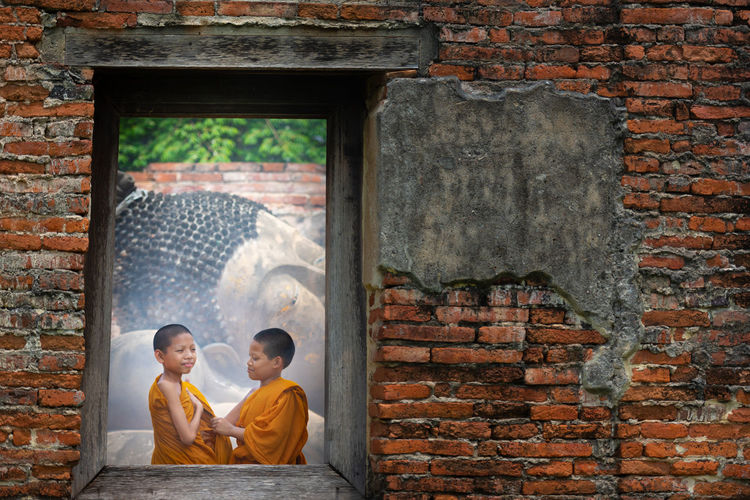Boys wearing traditional clothing seen through window