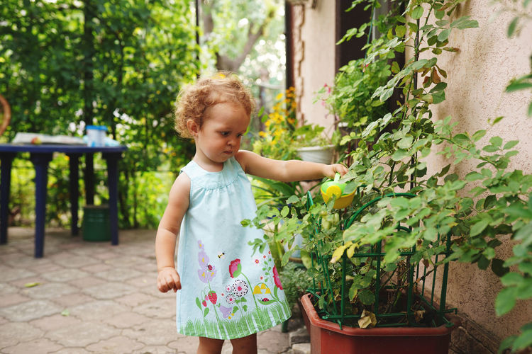 Cute girl standing against plants