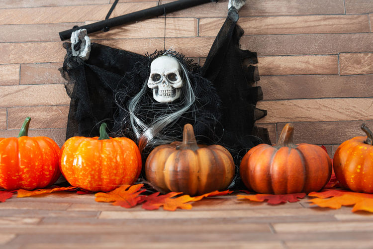 High Angle View Of Skull And Pumpkins On Table During Halloween