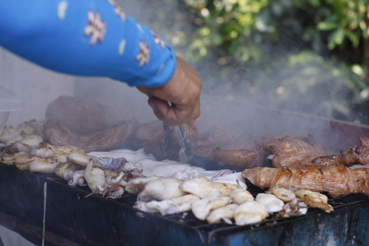 Person preparing food on barbecue grill