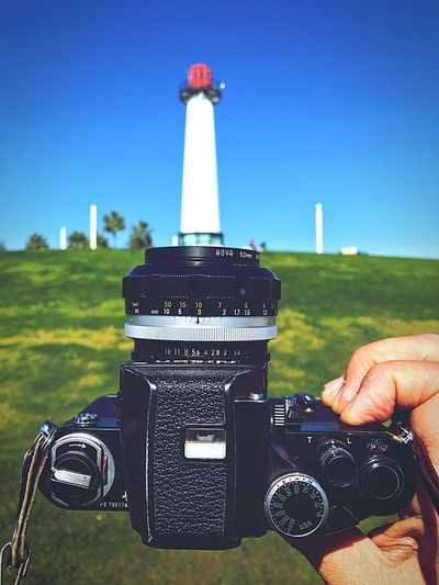 Cropped image of man holding camera against lighthouse