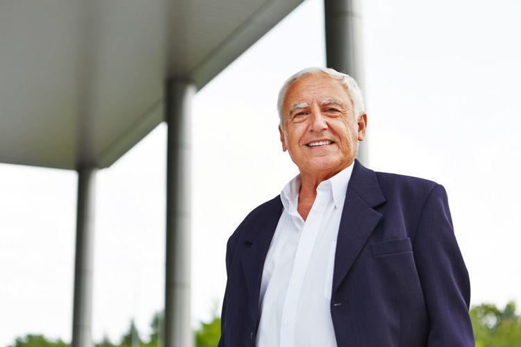 Portrait Of Smiling Senior Businessman Against Sky