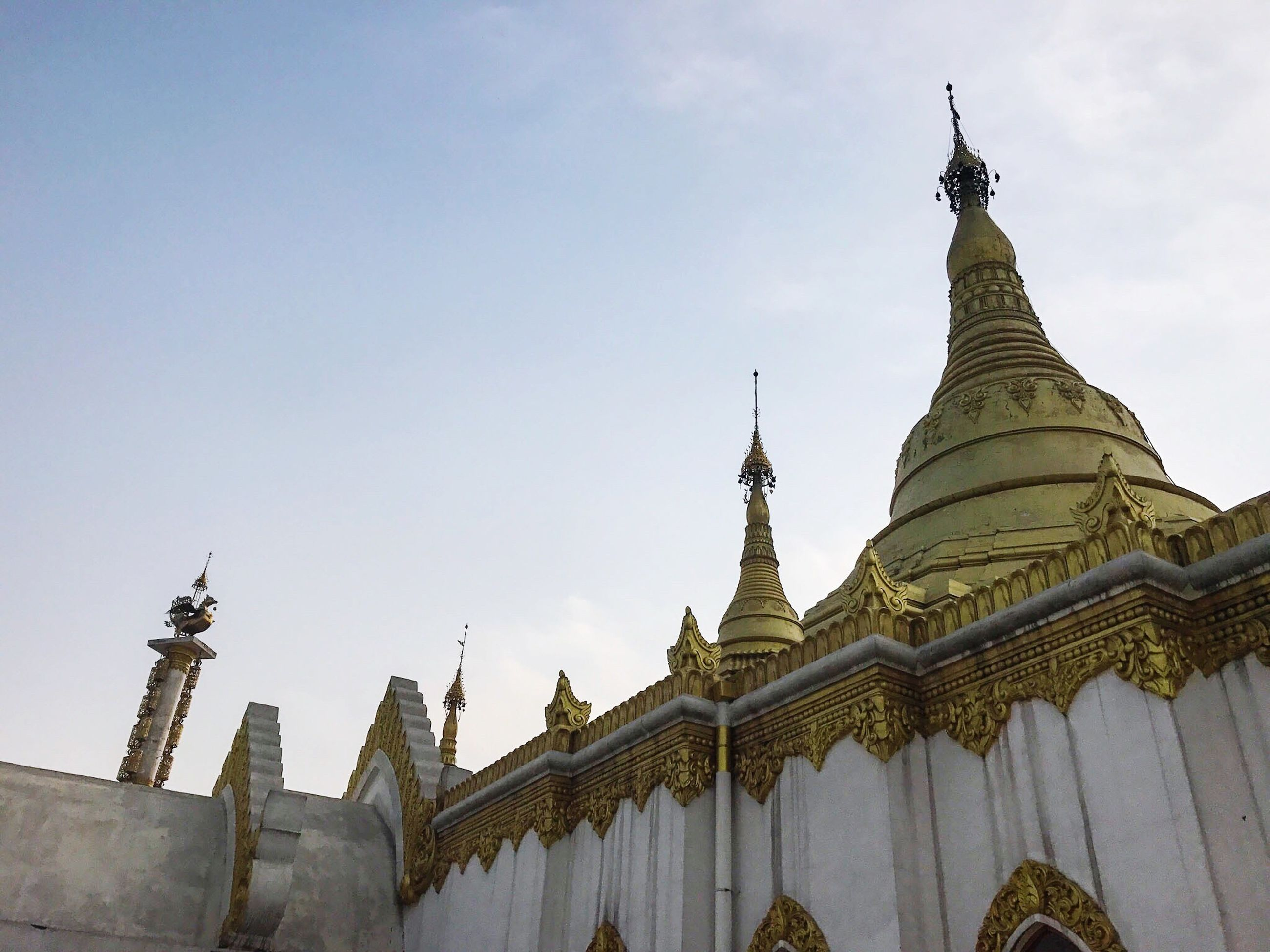 religion, spirituality, place of worship, low angle view, architecture, built structure, gold colored, no people, sky, building exterior, travel destinations, outdoors, gold, day