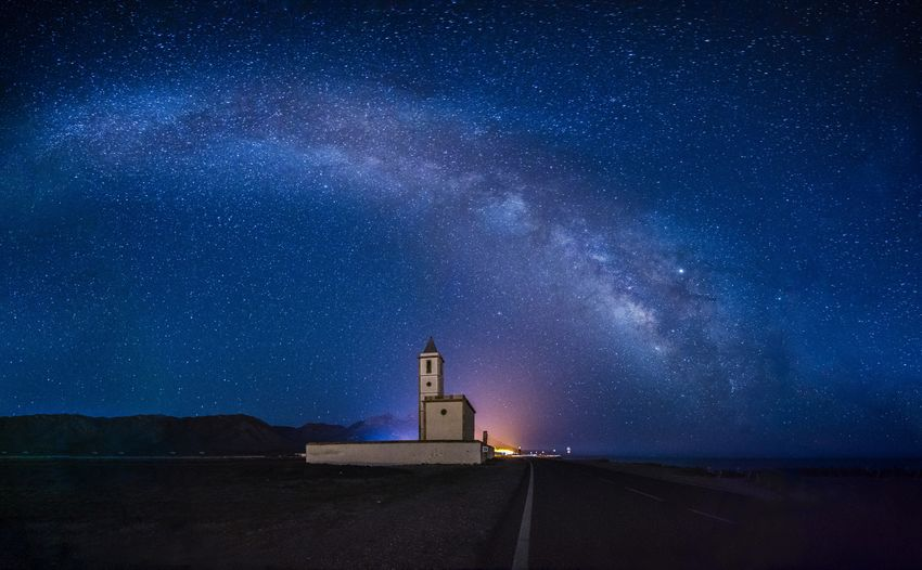 Lighthouse against star field at night