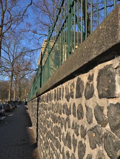 a school surrounded by a big high wall with above the wall another high fence. Pre War Building Defense School Playground Arnhem Wall - Building Feature Gate Fence Premium_collection