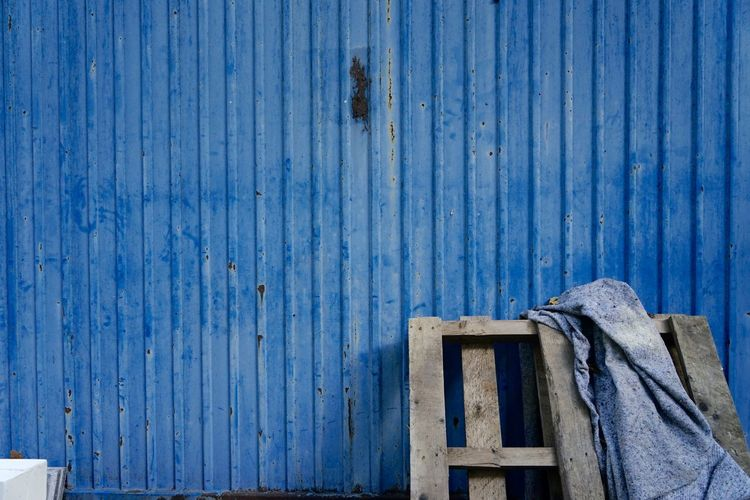 Fabric on pallet against blue fence