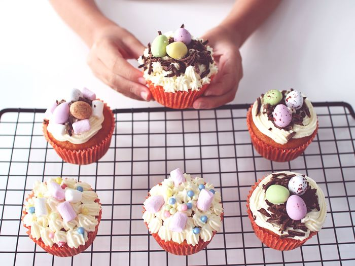 Cropped hands holding cupcakes on cooling rack at table