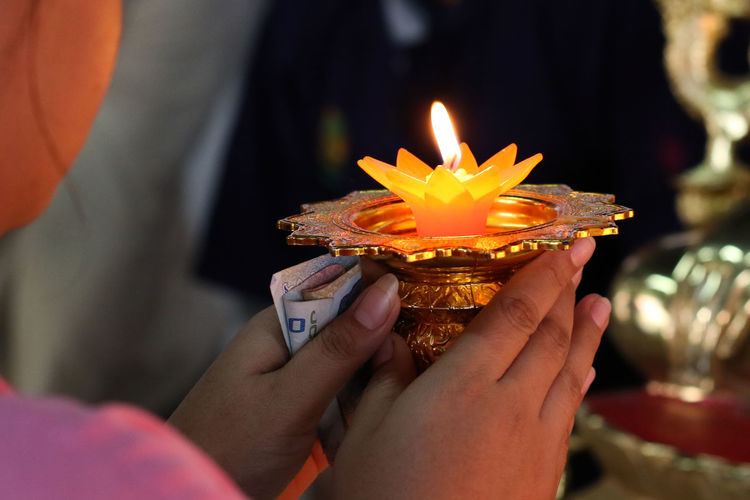 Close-Up Of Woman Holding Illuminated Diya